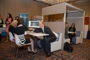 "Attendees at the Maine Real Estate & Development Association (MEREDA) conference test out the ""office of the future"" set up by Creative Office Pavilion to augment the conversation about the same topic, keynoted by two renowned architects from the design firm Gensler who traveled from Texas to speak at the event."