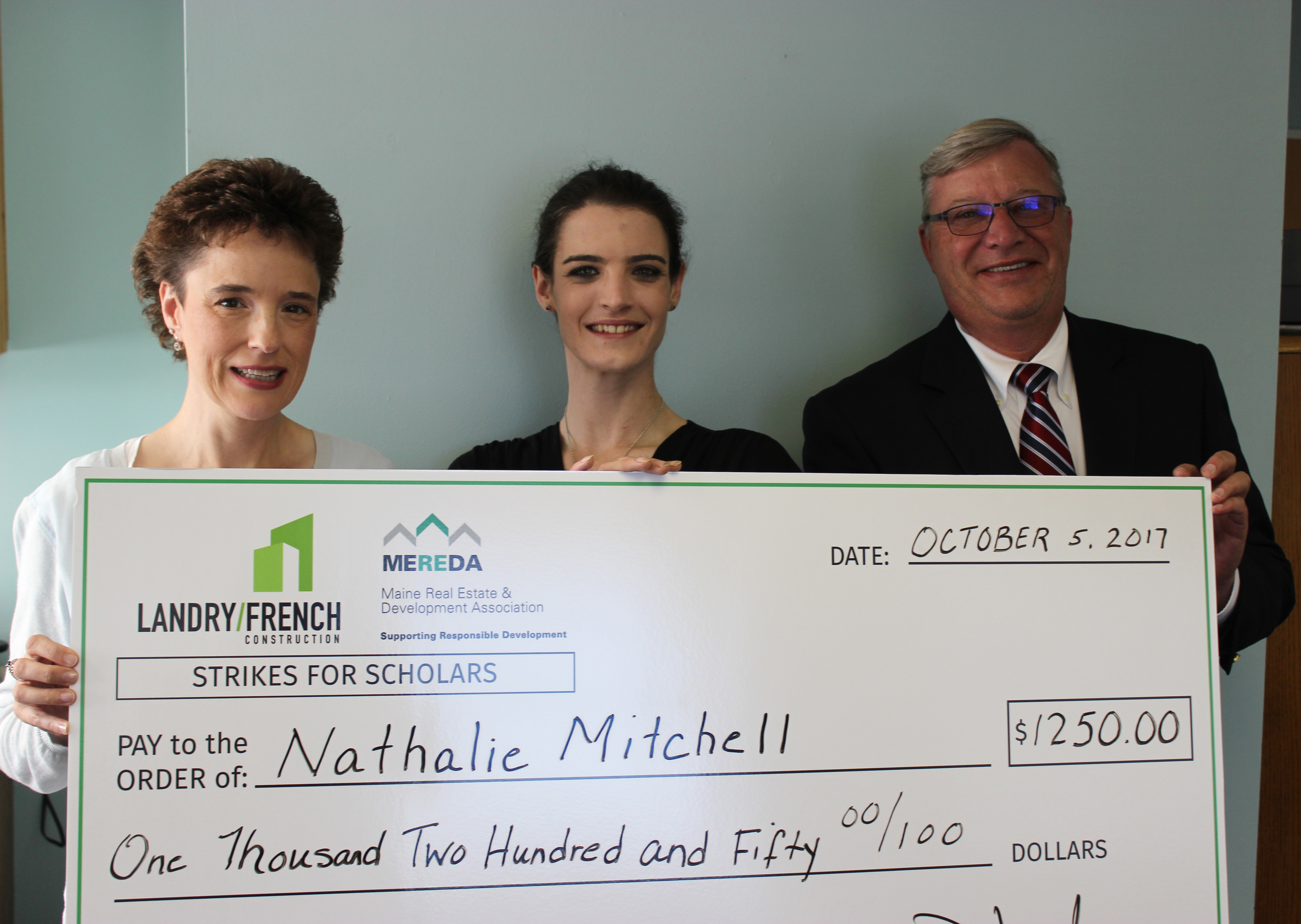 Shelly R. Clark from MEREDA and Denis Landry from Landry/French Construction present a scholarship check to SMCC Student Nathalie Mitchell.